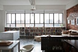 Offener Küchenbereich mit Sideboard, gegenüber Regal mit Büchern unter Fensterband in loftartigem Wohnraum