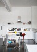 Designer Barhocker mit Schalensitz um thekenartigen Tisch in minimalistischer Küche