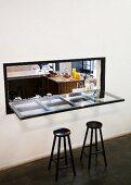 Schwarze Barhocker vor Glasplatte als Tischfläche in Durchreiche mit Blick in Küche