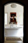 Blick durch Durchgang auf freistehende Badewanne und Ablage mit Blumen & Wandbild