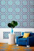 Auffällige Wandgestaltung mit einem Muster in der Art überdimensionierter, marokkanischer Fliesen mit farblich passendem Sessel und Beistelltisch