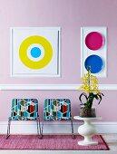 Wandgestaltung mit Kreisen und farbig lackierten Tabletts auf pastellvioletter Wand mit Zierleiste, davor bunte, geometrisch gemusterte Stühle und Säulentisch