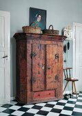 Old oil painting on top of rustic wardrobe made in 1800 next to antique pendulum clock above three-legged chair and black and white chequered tiles