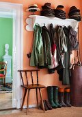 Collection of hats on coat rack, umbrella stand, chair and wellingtons in salmon-pink foyer; view of bust against lime green wall in living room
