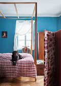 Bed with simple canopy and dog on gingham bedspread in bedroom painted sky blue