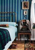 Period brass bedstead and Biedermeier chair against blue striped wallpaper