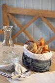 Frühstücksgebäck in selbstgefertigtem Brotkorb aus Jeansstoff auf Tisch in ländlichem Ambiente