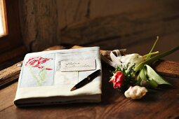 Book with hand-crafted, embroidered book jacket next to flowers on wooden surface