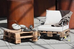 Coffee table and armchair hand-crafted from wooden pallets on terrace