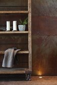 Vintage-style, wooden shelves on castors against corten steel wall