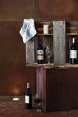 Wine bottles and glasses in wall cabinet made from sections of pallet on corten steel cube