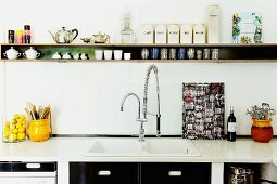 Narrow shelf and retro-look kitchen fronts as structural black elements in white kitchen