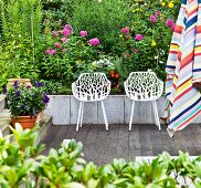 White, perforated shell chairs on terrace in front of flower bed; striped parasol in foreground