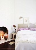 Doppelbett mit gepolstertem Kopfteil neben offenem Kamin in geweisselter Ziegelwand