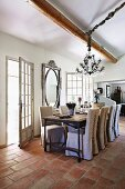 Chairs with loose covers at dining table next to open terrace doors in renovated country house with terracotta floor