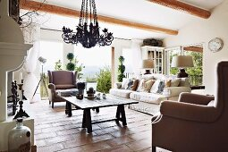 Armchairs and sofa around rustic wooden table on terracotta floor in country-style living room