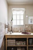Rustic washstand with sink against tiled wall below lattice window in country-style ambiance