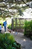 Man and child feeding hens on gravel path in front of wire mesh pen