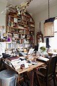Vollgestopftes Arbeitszimmer mit grossem, überladenem Schreibtisch und Bücherregal im Hintergrund