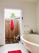 Modern bathtub in white bathroom, view of red towel hanging on wall of terrace screened with bamboo canes through open door