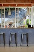 Metall Barhocker mit Retro Touch vor Theke und Blick durch Fenster auf Felswand