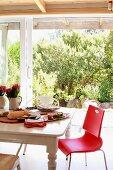 Roter Stuhl an rustikalem Holztisch mit angerichteten Vorspeisen; Blick durch Terrassenfenster in sonnenbeschienenen Garten