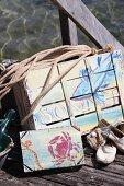 Mit Acrylfarbe sommerlich maritim bemalte, alte Obstkisten auf Holzsteg am Seeufer