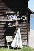 Bretter mit verknotetem Juteseil als selbstgebautes Hängeregal mit Blauweissgeschirr an Bootshausfassade befestigt