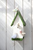 Wooden birdhouse with hand-crafted birds made from undyed wool felt