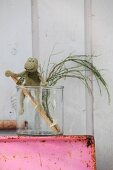 Hand-felted frog on ladder made from sticks in glass vase
