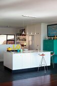 Reihe mit Pendelleuchten über Kücheninsel mit Spüle und Barhockern; türkisfarbener Schrank an einer Seite der offenen Küche