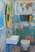 Mit Landkarten beklebte Wände in Gäste-WC mit goldgerahmtem Ovalspiegel über modernem Waschbecken