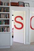 Von Einbauregalen umrahmte Zimmertüren, verziert mit roten Buchstaben