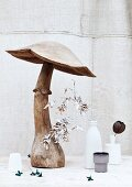Large, wooden mushroom ornament and painted plants in vases