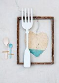 Still-life arrangement of vintage fork on wooden picture frame with painted leaf and spoons stuck down with tape