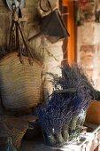 Getrocknete Lavendelsträusse im Drahtkorb vor an rustikaler Wand gehängte Einkaufstasche
