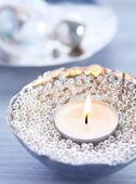 Schale mit Silberperlen gefüllt und mit Teelicht