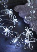 Aus länglichen Perlen selbst gebastelte Blüten an einer Lichterkette