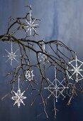 Mit Perlen verzierte Drahtsterne als weihnachtliche Dekoration an einem Zweig