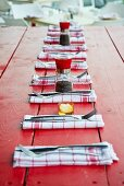 Folded red and white linen napkins, cutlery, pepper mills and salt cellars on red-painted garden table
