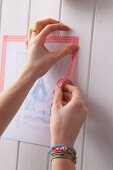 Woman sticking picture of Paris with decorative masking tape