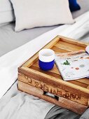 Beaker and magazine on upturned wooden crate used a breakfast tray on bed