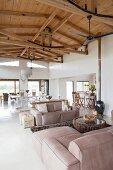 Langgestreckter Wohnraum mit sichtbarer Dachkonstruktion aus Holz; Sitzbereich mit Polstermöbeln