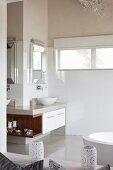 Übereck-Waschtisch mit gerahmten Spiegeln und integriertem Holzregal in hellem Bad mit poliertem Zementboden
