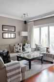 Framed, landscape-format mirrors and mirrored curtain rails in seating area with patterned scatter cushions and blanket with wide stripes on beige sofas