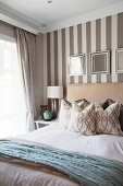 Framed mirrors on elegant wallpaper with broad stripes behind double bed with upholstered headboard