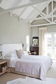 Double bed with white bed linen in attic room with exposed, white roof structure