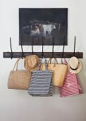 Gestreifte Taschen und Sommerhüte an Vintage Wandhakenleiste unter Ölbild mit Kuhmotiv