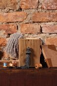 Wooden box and haberdashery items on chest of drawers against rustic brick wall