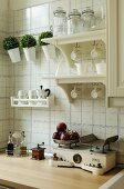 Cups hanging from hooks below shelves mounted on tiled wall above antique kitchen scales on wooden worksurface